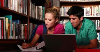 Studenten, die auf dem Boden der Bibliothek liegen und zusammen lernen