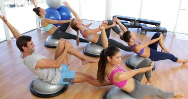 Fitness class lying on bosu balls together