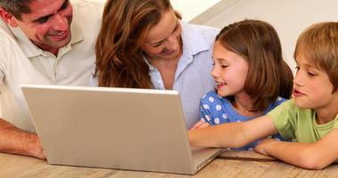 lächelnde Familie mit Laptop zusammen am Tisch