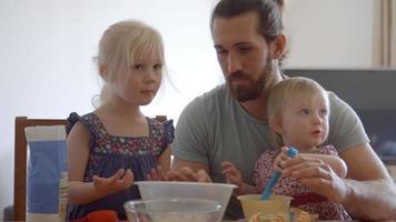 pai com filhas em casa fazendo bolos juntos video