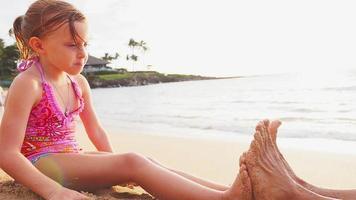 Vater und Tochter spielen zusammen am Strand
