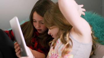 amici preadolescenti che usano i loro tablet insieme a casa video