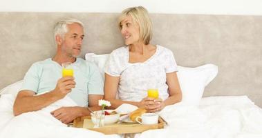 Paar, das zusammen im Bett frühstückt