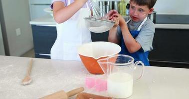 irmãos sorridentes fazendo um bolo juntos video