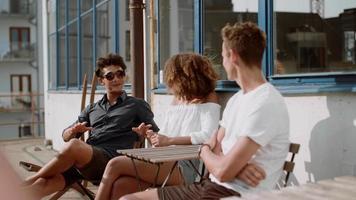 três jovens amigos juntos em um café ao ar livre video
