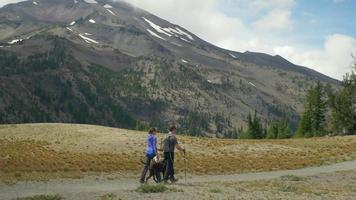deux randonneurs et leur chien marchent ensemble