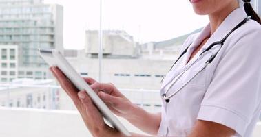 Krankenschwester in Tunika mit Tablet-PC und Lächeln in der Kamera