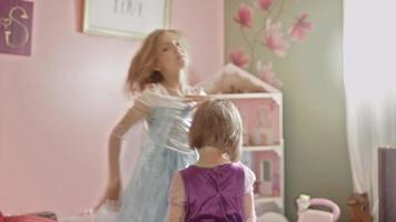 Two little girls wearing princess dresses playing together video