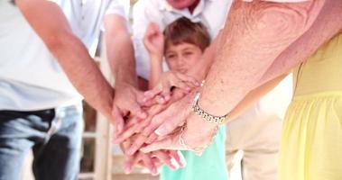 Familie, die ihre Hände auf einem Stapel zusammenlegt