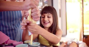 Little girl and her mom making cupcakes together