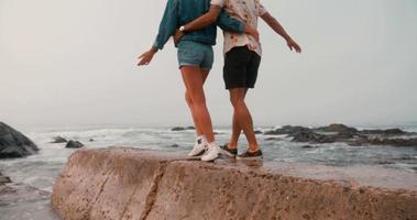 coppia hipster che camminano insieme su una parete del mare