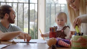 família sentada à mesa e fazendo desenhos juntos video