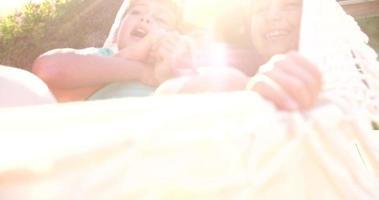 mãe amorosa e filhos rindo juntos em uma rede