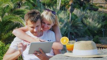 giovani coppie che parlano a un tablet, chat video. sullo sfondo di piante tropicali e palme. sempre connesso in vacanza