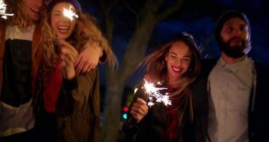 Hipster teen friends celebrating together with sparklers at night