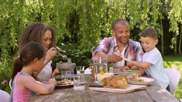 Familia en casa comiendo comida al aire libre en el jardín juntos video