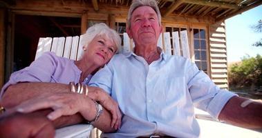 casal de idosos aposentados de mãos dadas e sentados ao ar livre