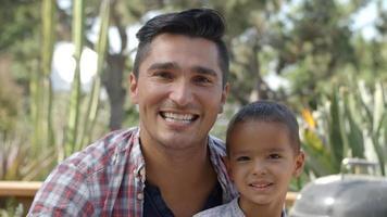 retrato de pai e filho sentados no jardim juntos video