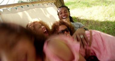fotogene multiethnische Familie, die zusammen auf einer Hängematte entspannt