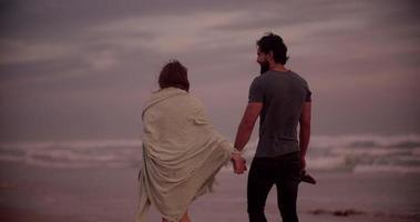 couple main dans la main en marchant le long d'une plage ensemble