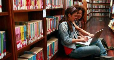 lächelnde Studenten, die zusammen auf dem Boden in der Bibliothek sitzend studieren