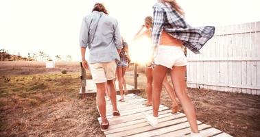 grupo de adolescentes caminhando juntos ao pôr do sol com o clarão do sol