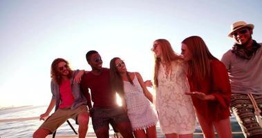 Grupo multiétnico de amigos en yate juntos al atardecer