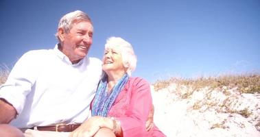 Laughing retired couple sitting on sand at the beach together