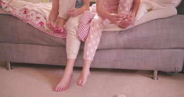 adolescentes de pijama na cama pintando as unhas dos pés juntas video