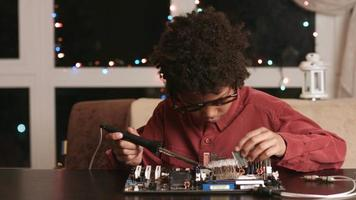 Surprised black boy fixing motherboard. video