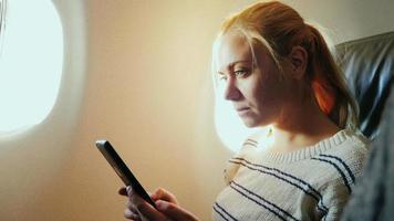 mujer joven que viaja en un avión, usa tableta