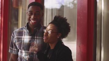 coppia afro-americana in posa insieme davanti a un edificio rosso