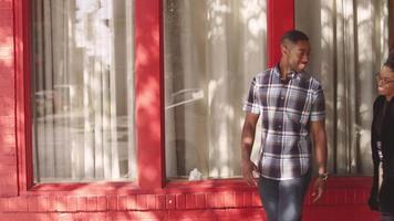 African American paar poseren samen voor een rood gebouw