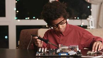 Afro boy soldering motherboard. video
