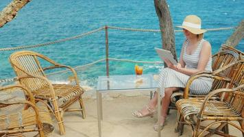 Woman tourist speaks with the tablet, always-on connection. Videochat of scenic spot overlooking the sea