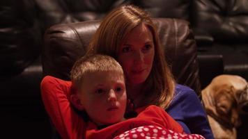 una madre e un figlio seduti insieme a guardare un film in un home theater