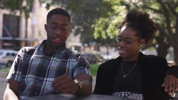 Pareja afroamericana en una mesa al aire libre hablando y riendo juntos, con bokeh video