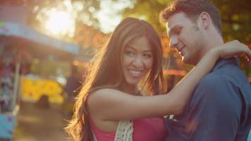 una coppia che balla insieme a una fiera mentre il sole tramonta dietro di loro video