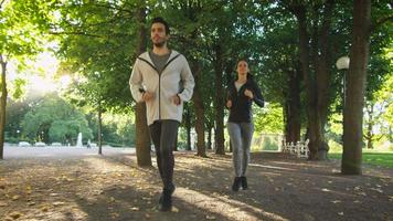 mulher e homem correndo juntos para a frente em direção à câmera em um dia ensolarado