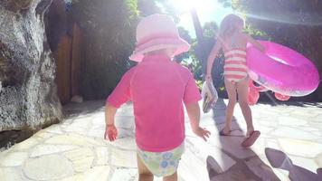 Familie zu Fuß zu einem Pool mit Poolspielzeug