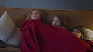 três irmãs sentadas em um sofá compartilhando um cobertor e assistindo tv