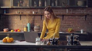 junge Dame, die Computer benutzt und Mittagessen kocht