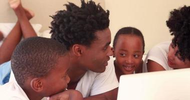 glückliche Familie, die Computer beobachtet