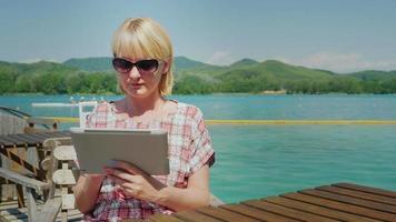 mujer joven con la tableta. sentado en un café en la terraza al fondo del pintoresco lago y las verdes montañas. España video