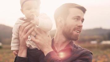 Ein junger Mann hält sein Baby an einem Herbsttag hoch draußen mit Linseneffekt video