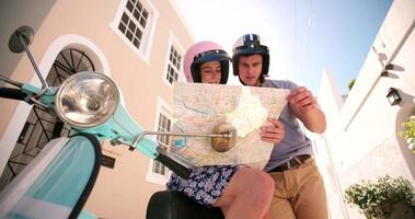 Pareja usando el mapa durante un viaje por carretera con su scooter