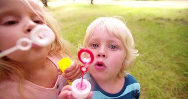 ragazza e ragazzo che soffia bolle nella fotocamera video