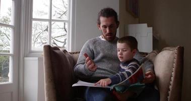 padre se sienta en una silla en casa leyendo un libro al hijo filmado en r3d