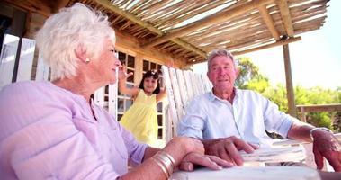 niña riendo con sus abuelos al aire libre con la llamarada del sol