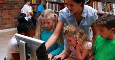 élèves regardant l'ordinateur dans la bibliothèque avec leur enseignant